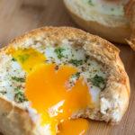 Gebackenes Ei im Brötchen Nahansicht mit flüssigen Eigelb